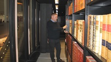 A man retrieving a book from the King's Library