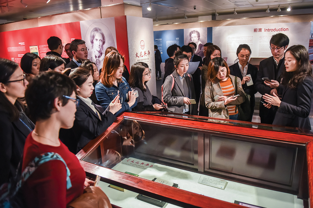 People looking at an item in exhibition case.