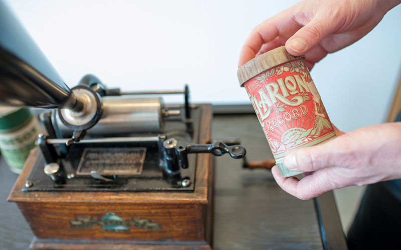 Wax cylinder being held in front of a phonograph.