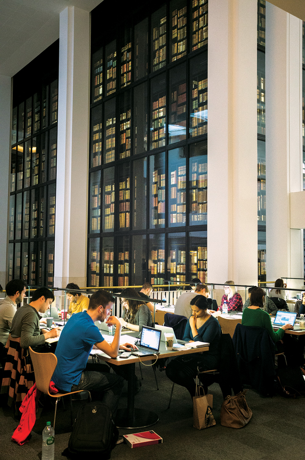 People studying at desks in front of the King's Library inside the British Library.