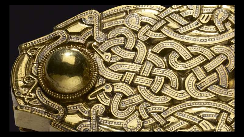 A detail of the Sutton Hoo belt buckle, made from gold and featuring a web of intertwined snakes.