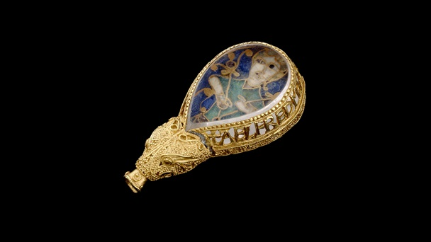 The front of the Alfred Jewel, made from gold, and featuring a socket in the form of an animal head and an enamelled figure of a man set beneath rock crystal.