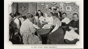 Photograph of the interior of the Ayahs Home in Hackney, where women are sat around a table doing needlework and crafts
