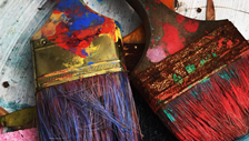 Photo of two paint brushes covered in paint