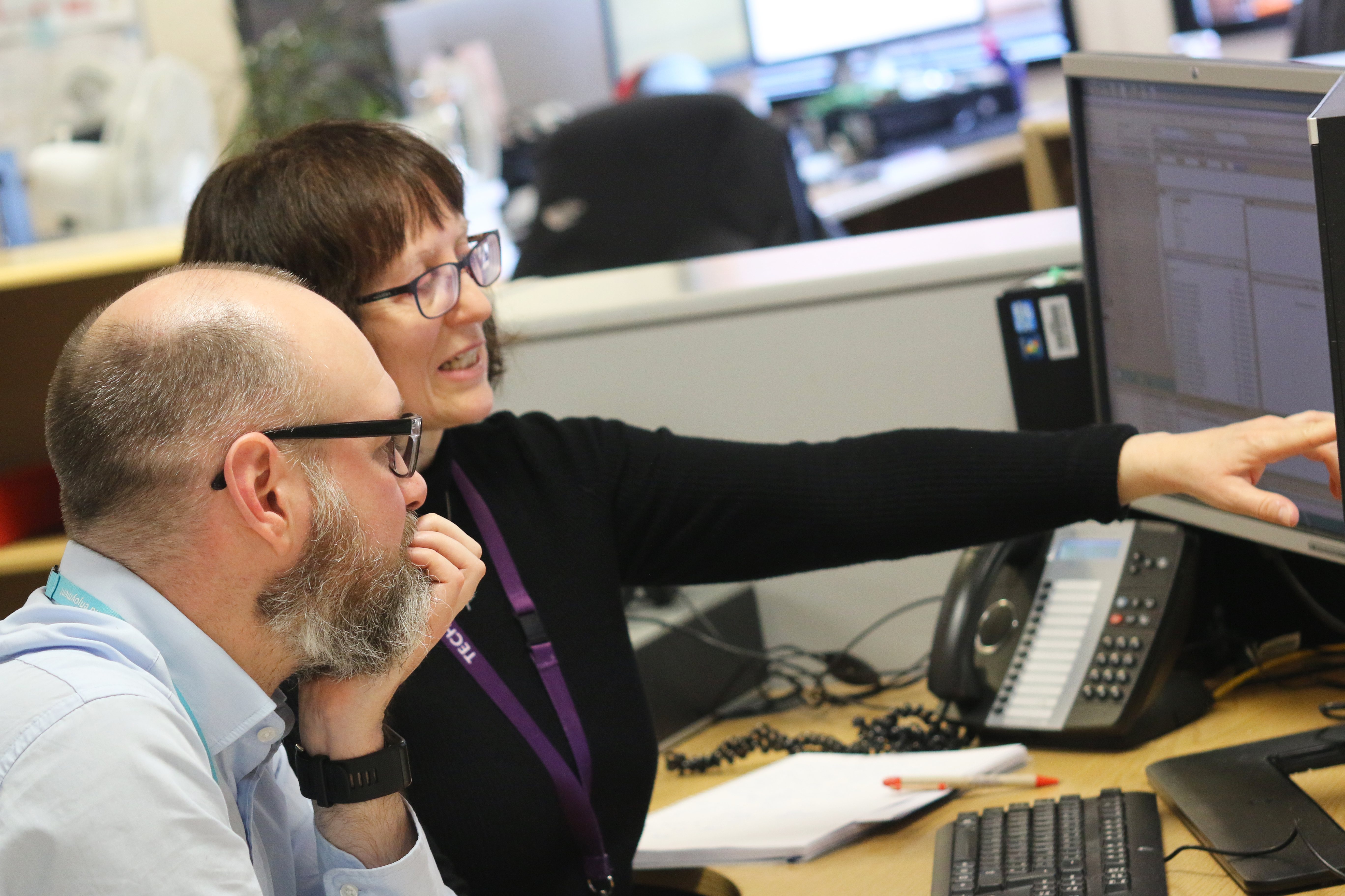 Two Application Support team members at a PC