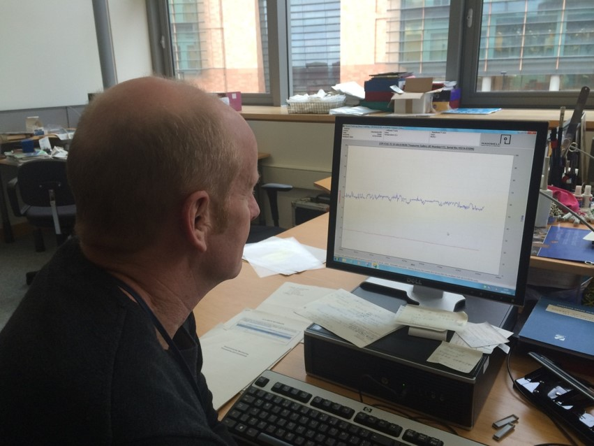 Man looking at a graph on a computer screen.