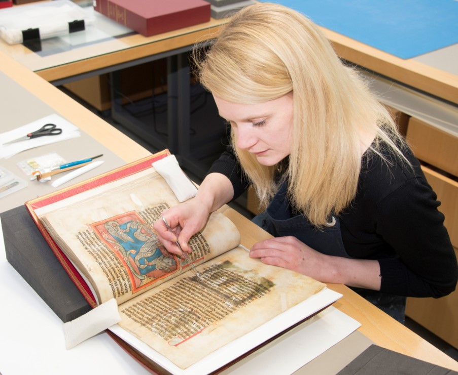 A conservator working on an illuminated manuscript.