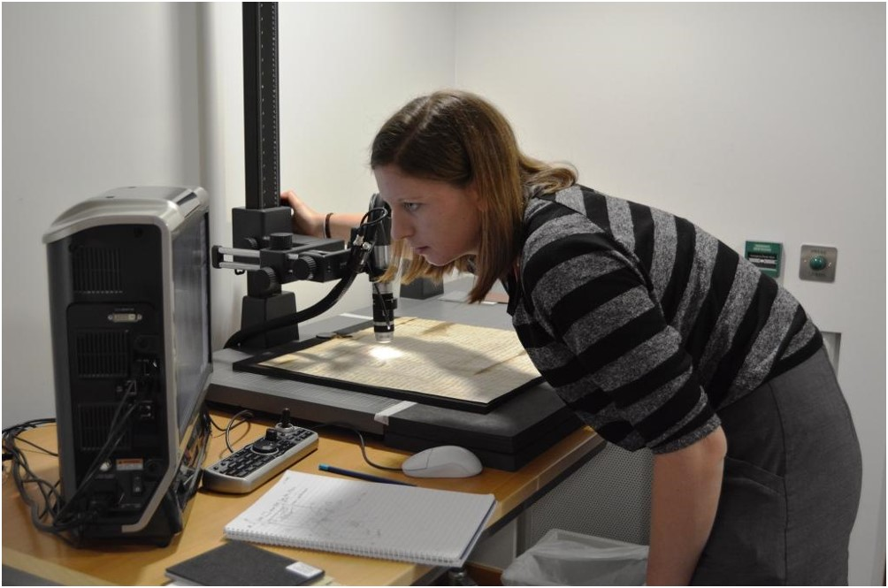 Conservator with an electric microscope looking at a display screen.