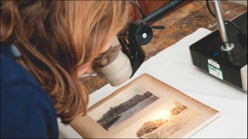 Conservation expert examining a photograph with a microscope.