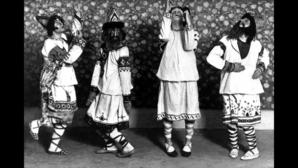 Photograph of four performers in costume and masks from Stravinsky's ballet The Rite of Spring
