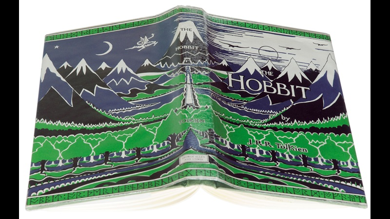 Dustjacket of The Hobbit, with an illustration depicting forest, mountains and a dragon flying through the air.