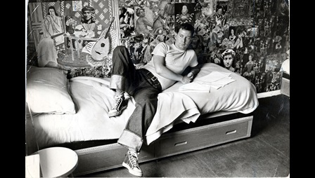 Joe Orton at his flat in Islington. The wall behind him is plastered with a collage of images from books and magazines.