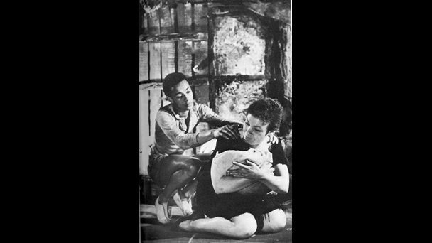 Black and white photograph of Cleo Laine and Tamba Allen in the 1958 premiere of Flesh to a Tiger by Barry Reckord. Laine, playing Della, is kneeling on the floor closely holding a baby while Allen crouches behind her and holds her shoulders