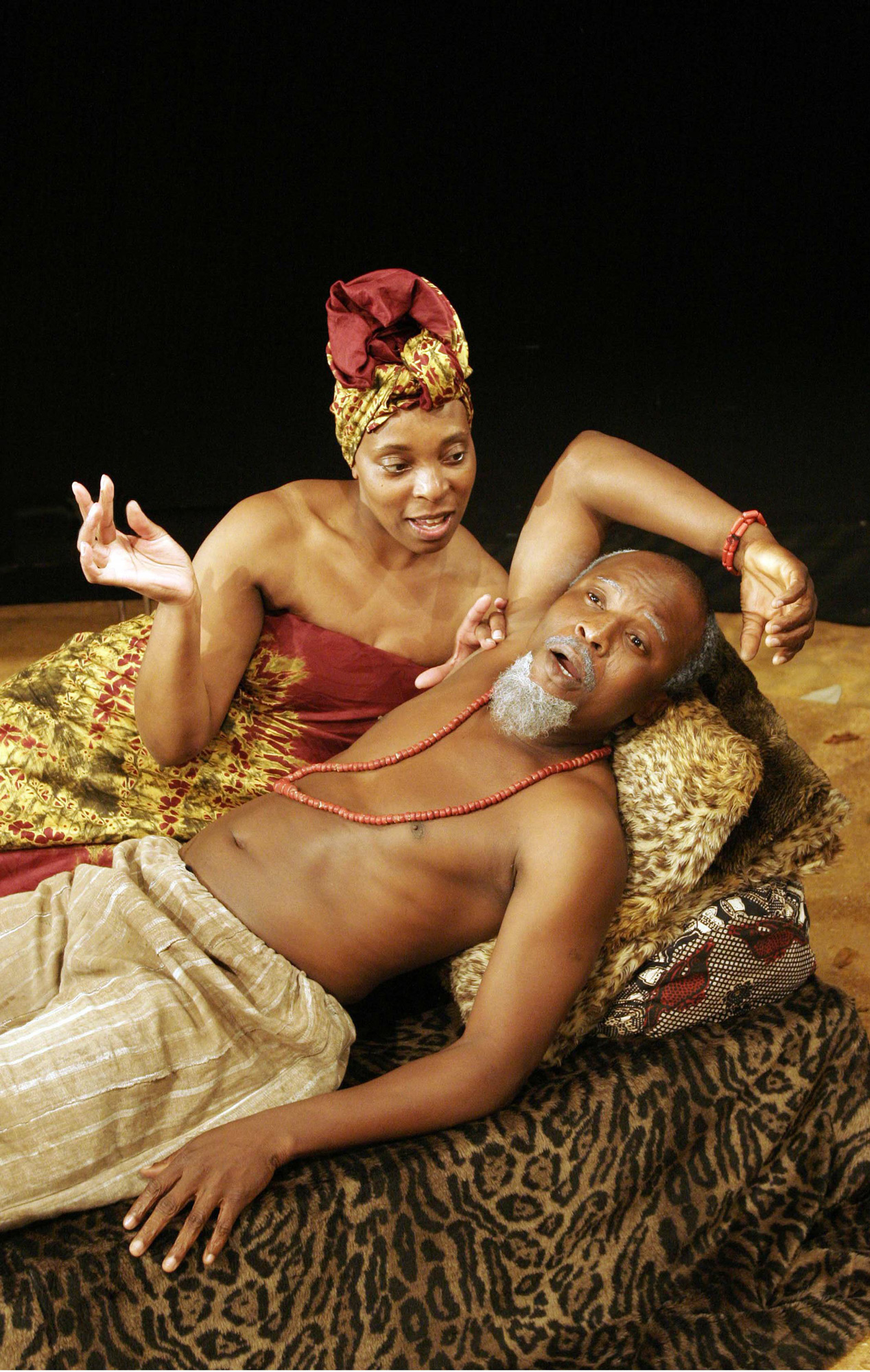 Colour photograph of Louisa Eyo as Favourite and Toyin Oshinaike as Baroka, both lying on a couch in conversation, in a production of The Lion and the Jewel, 2005