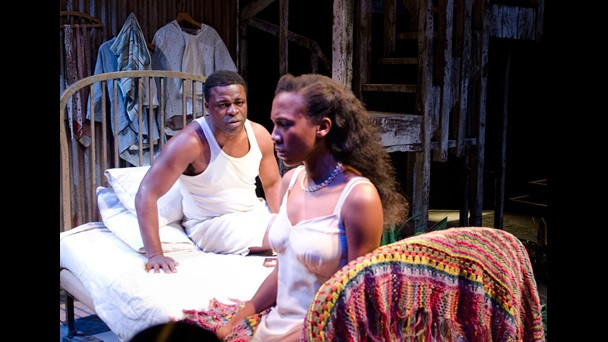 Photogragh of Danny Sapani as Ephraim and Jade Anouka as Rosa sitting on a bed, in the 2012 National Theatre production of Moon on a Rainbow Shawl