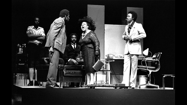 Black and white photograph of a scene from the 1974 production of Play Mas. Lucita Lijertwood as Mrs Banks is shouting at Rudolph Walker's character Samuel, watched by Norman Beaton as Frank