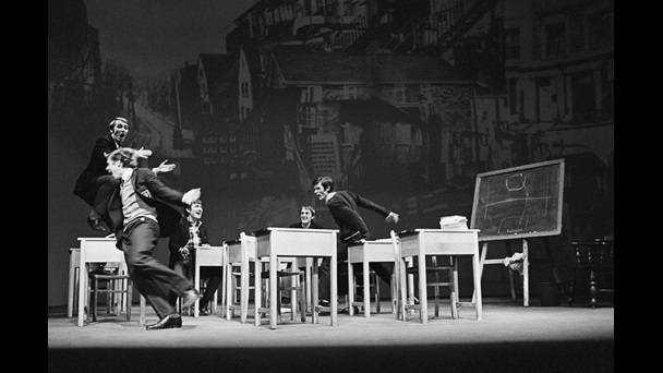 Black and white photograph of a classroom scene from Skyvers by Barry Reckord, 1968 revival at Nottingham Playhouse. A pupil runs around while 3 others cheer him on, the backdrop is a photograph of a street.