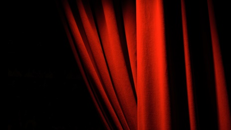 Drawn back red theatre curtain