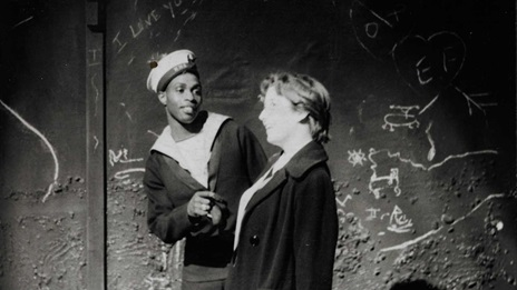 Photograph of Jo and Jimmie talking, from a production of A Taste of Honey. Jimmie is in a sailor's outfit