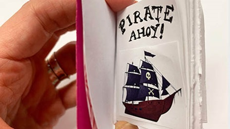 open miniature book showing illustration of a pirate ship