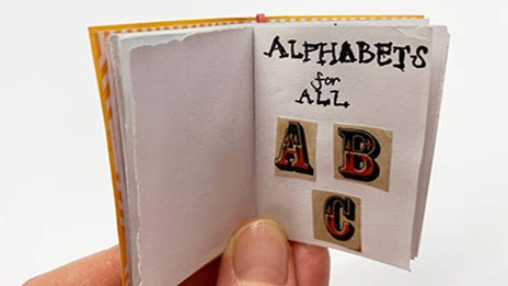 open miniature book showing the letters A B C