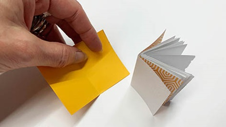 a cover being held up to a miniature book