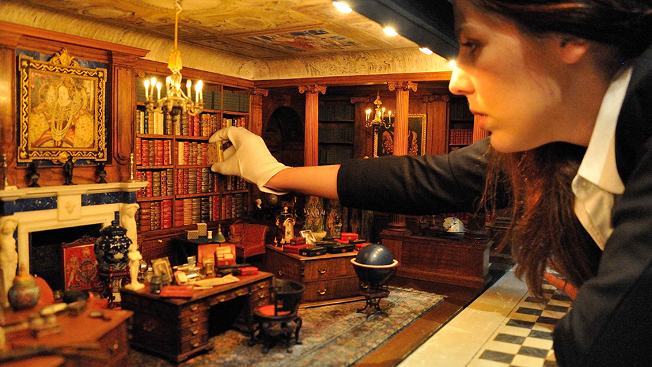 A curator takes a book from Queen Mary's Dolls' House library