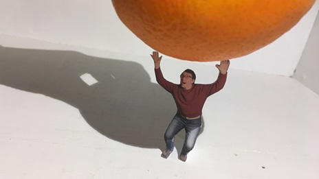 A cut-out figure placed beneath an orange