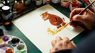 With pens and art equipment scattered across a desk, in the middle of the frame is an illustration of the Gruffalo.