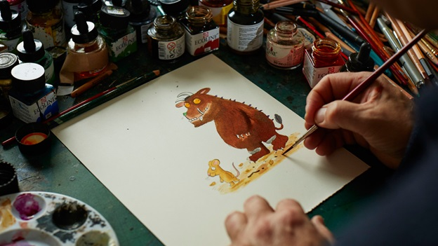 Photo of Axel Scheffler drawing a Gruffalo on paper at his studio desk. He holds a paint brush in his right hand and is surrounded by pots of ink.