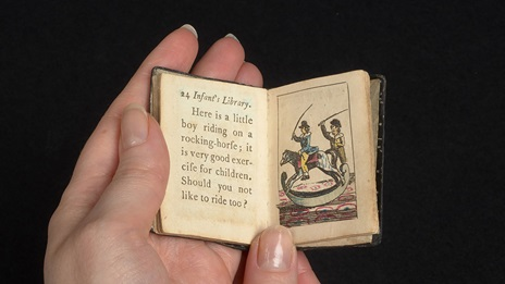 A adult's hand holding an open a miniature book