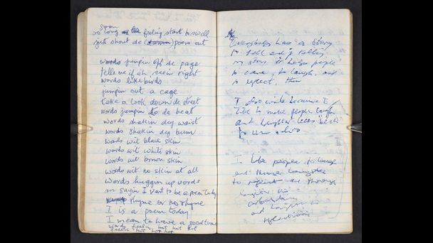 Open notebook. John Agard's handwritten drafts of poem. The notebook paper is lined, the writing is in blue ink.