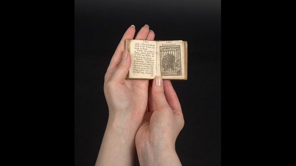 A small book being held in a pair of hands. The book is open. The right hand page depicts a very large porcupine inside a cage.