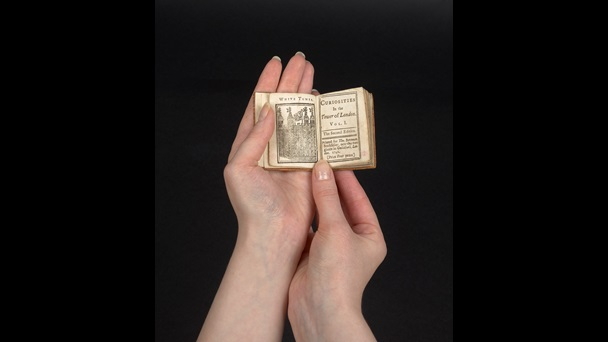 A small book being held in a persons hands. The book is open. The left hand page shows a black and white illustration of the the White tower, Tower of London. The right hand page is the title page for volume 1 of 'Curiosities in the Tower of London'