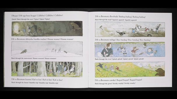 Pages 13-14 of We're Going on a Bear Hunt. The text is written in English and Somali. Each page has three landscape images to be read from top to bottom, per page. Image 1 - the family tiptoe out of the cave as a bear runs towards them. Image 2 - the bear chases the family through a snow field. 3 - the bear chases the family through woodland. 4 -  the bear chases them through mud pools. 5 - the bear chases them through a deep river. 6 - the bear chases them through long grass which  is waist height on the adults.