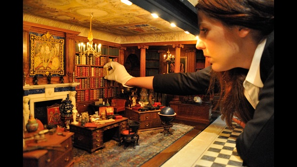 A curator wearing white gloves leans into the Library of Queen Mary's Dolls House. The curator is taking a book off the shelves from the back wall of the room.