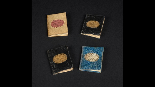 Four volumes from The Infant's Library lying on a black background. Two have black covers, one has a yellow/cream coloured cover and one has a blue cover.