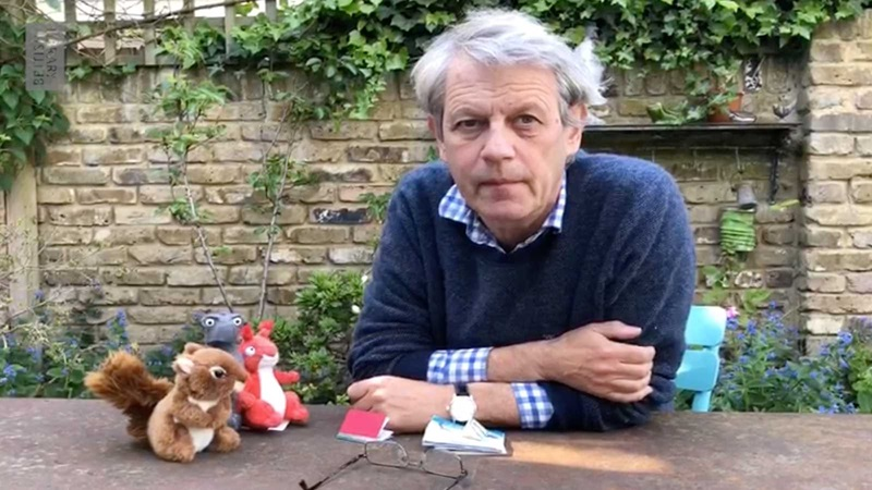 Image of Axel Scheffler in his garden with a miniature book and two toy squirrels