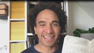 Photograph of Joseph Coelho. He is smiling directly into the camera and holding up one if his handwritten poetry notebooks