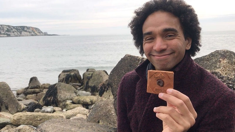 Photograph of Joseph Coelho standing with the sea behind him, he is holding a miniature book.