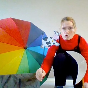 Storyteller Dani is crouched in front of a rainbow umbrella. She is holding a flag cut in to the shape of a crescent moon.