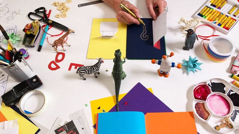 Craft materials and small animal figurines arranged on a white surface. The animals 'watch' A pair of adult hands is drawing in a card