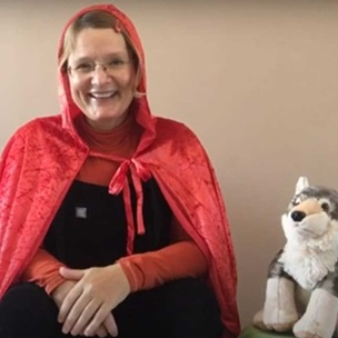 A women wearing a red hooded cape sits on a chair smiling at the viewer. Beside her is a soft toy wolf