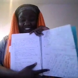 Ruth Awolola holds a notebook open and shows it to the camera