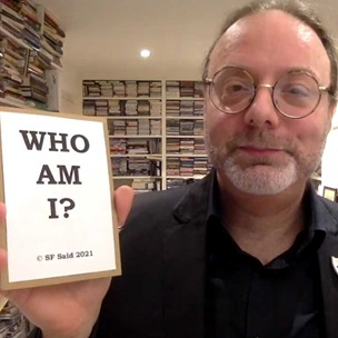 Author S F Said stands in a room shelved with lots of book. He holds up a handmade book titled 'Who Am I?'.