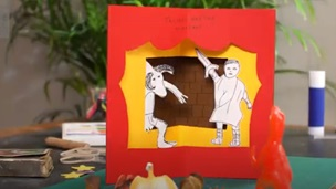 Photo of a completed theater pop-up book page. The page depicts Red curtains with a Minotaur climbing through a window. A man in a toga waves a sword at the monster.