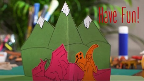 Photo of a completed V fold pop-up book page. The page has pop-up green mountains in front of which are a pink dragon and an orange wizard