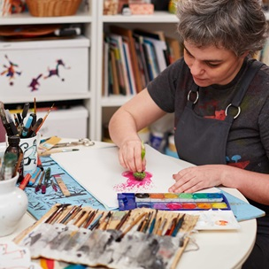 a lady in a artists studio working on a picture