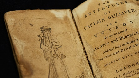 Crop of an edition of The Adventures of Captain Gulliver, open at the title page with a facing illustration of Gulliver