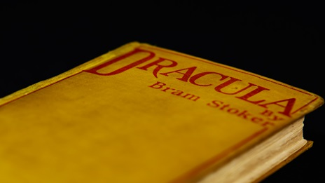 Shot of the first edition of Dracula by Stam Stoker, the cover features red text on a yellow background